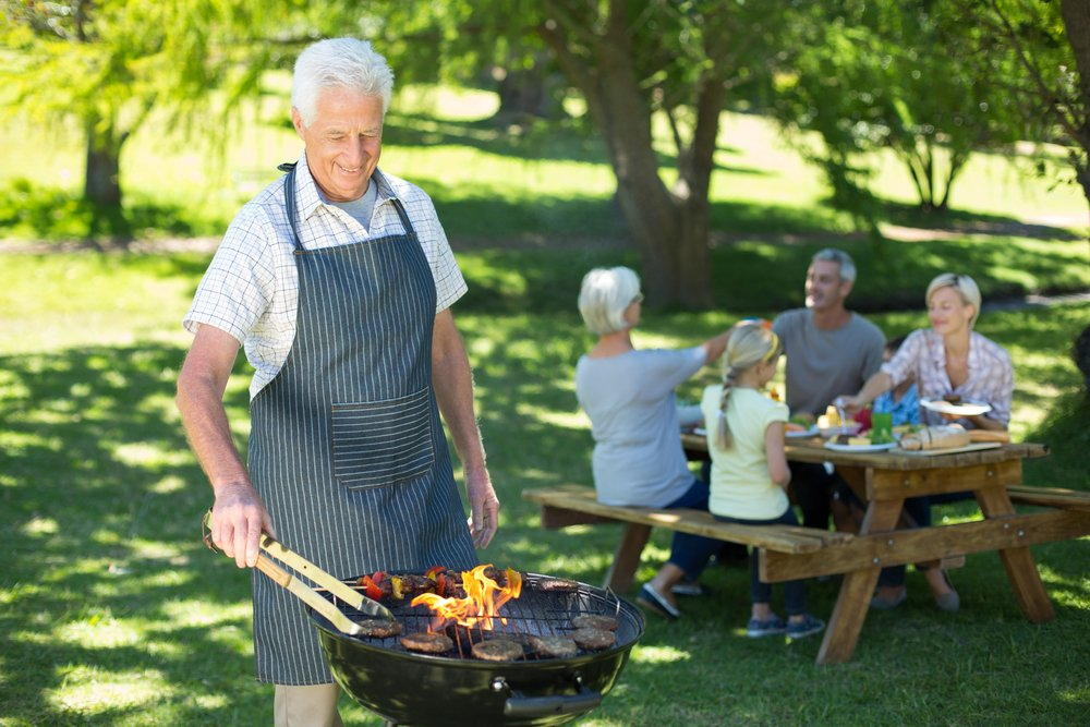 Happy grandfather doing barbecue on a sunny day